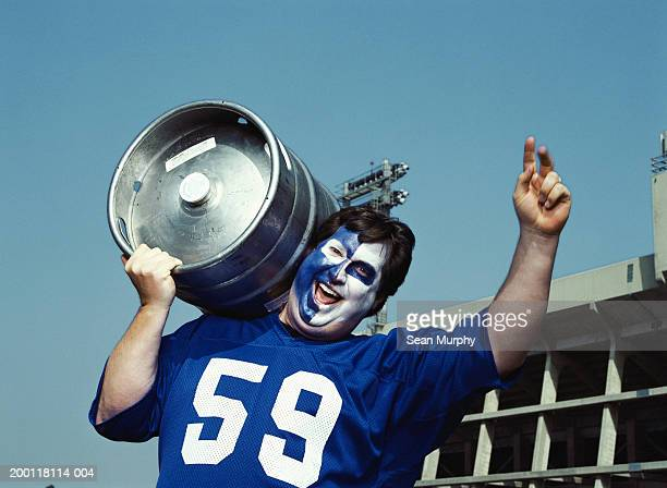 Man with painted face holding beer keg