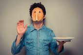 Young man has cut eyeholes in a pancake and is wearing it on his face