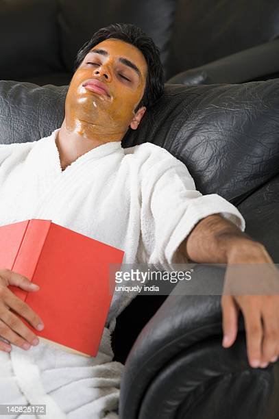Man with peel off mask resting on a couch