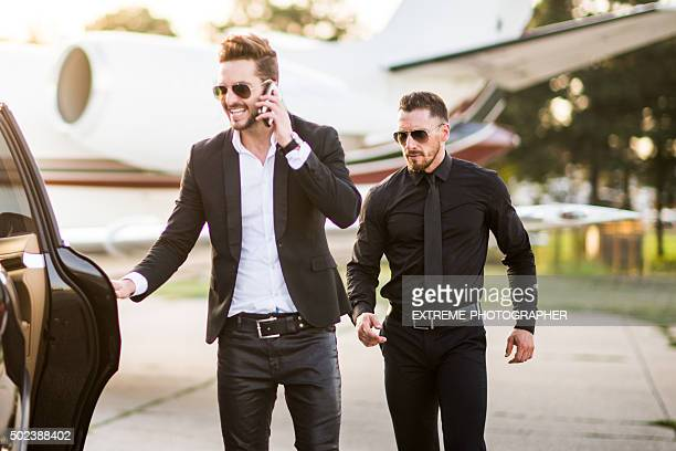 Man with phone escorted by his bodyguard