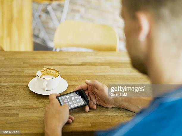 Man with phone in cafe
