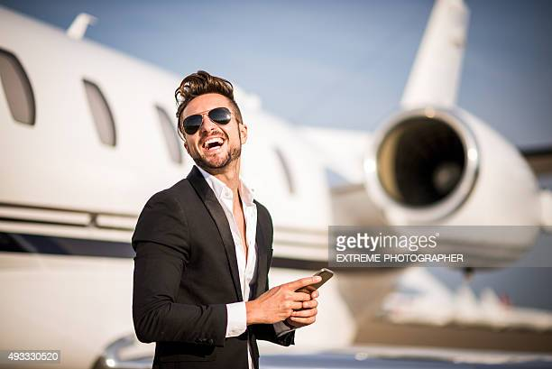 Man with phone next to private airplane