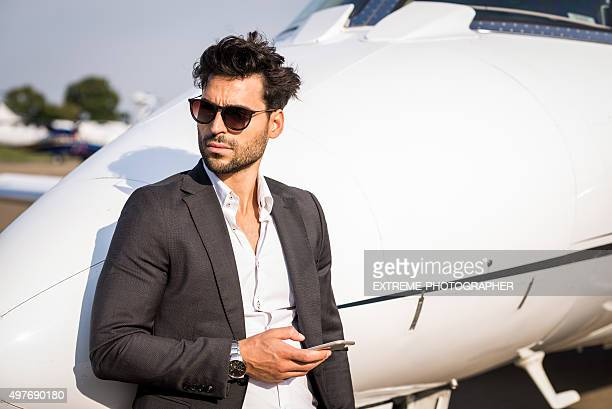 Man with phone next to private jet aeroplane
