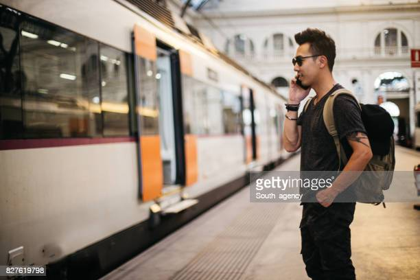Man with phone standing at train station
