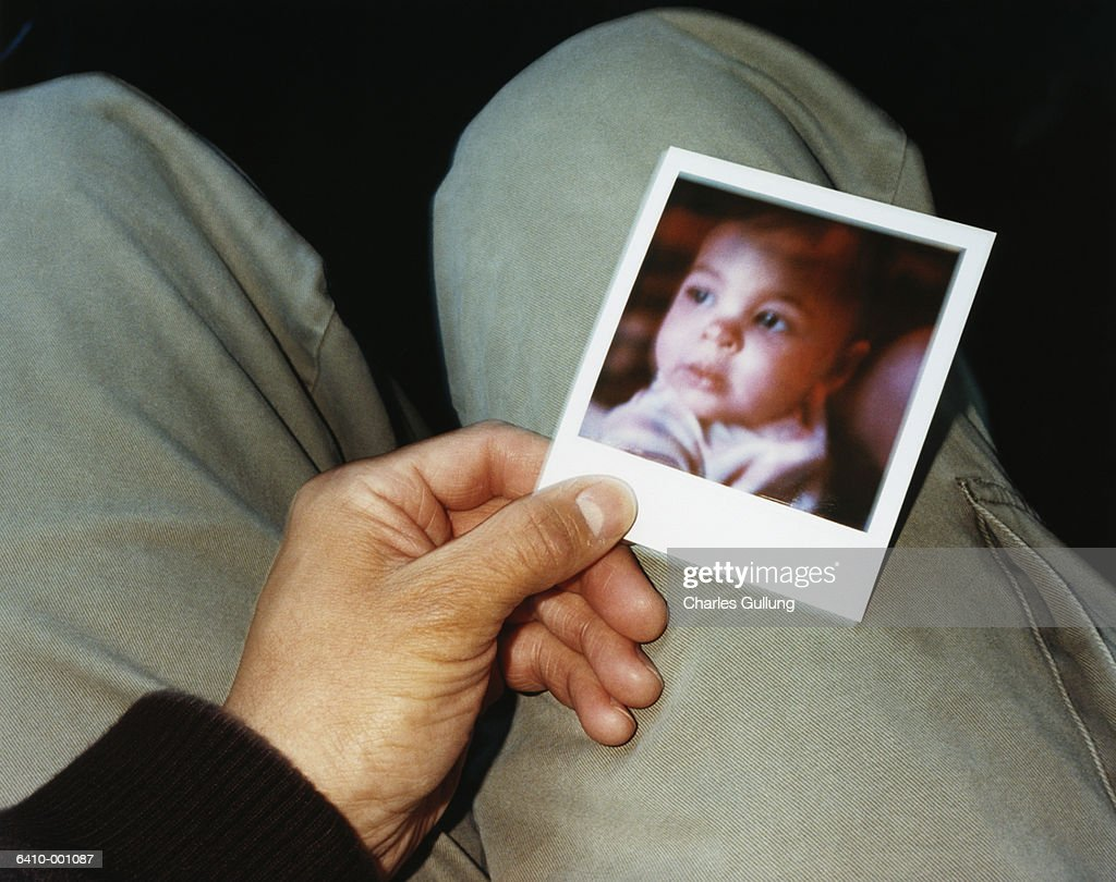 Man with Photograph of Baby : Stock Photo