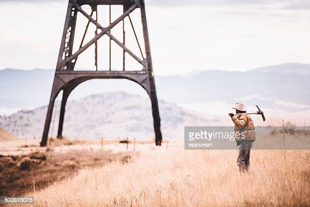 Man with pickaxe looks at oil drill in western plain