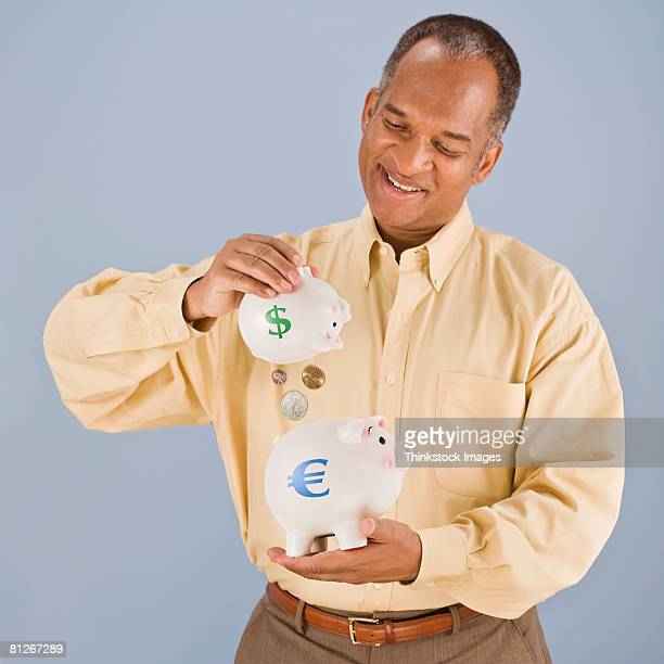 Man with piggy banks and coins