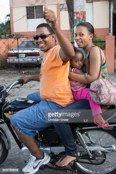 Santa Domingo Dominican Republic November 30 2012 A man with probably his wife and child on a motorbike is giving a 'thumbs up' in the poor...