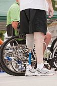 Man with prosthetic leg standing with a man in wheelchair with spinal cord injury