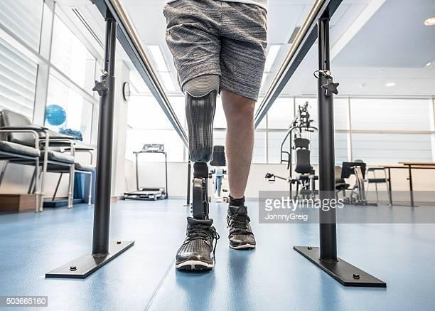 男性、義足パラレルバーを使用