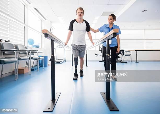 Uomo con una protesi alla gamba con Barre parallele con physyiotherapist