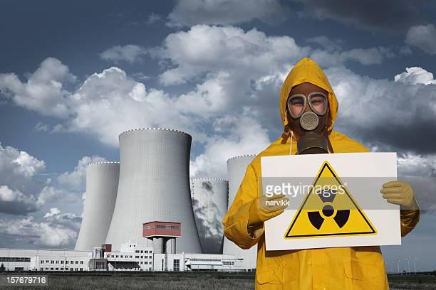 Man With Radioactive Sign in Front of Nuclear Reactor