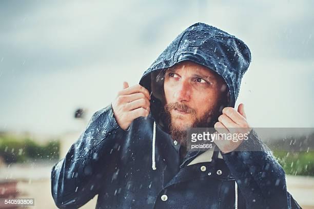 男性、レインコート大雨の下