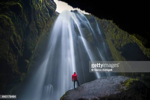 Man with red coast standing on top of a rock under Gljúfrafoss waterfall, Southern Iceland, Iceland, Northern Europe.