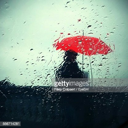 Man With Red Umbrella Walking Against Sky Seen Through Wet Glass During Monsoon