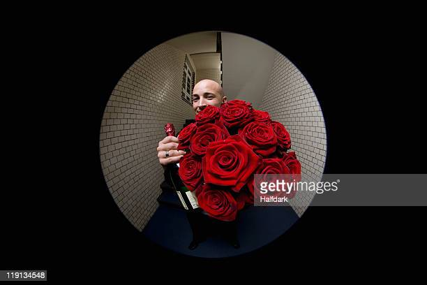 A man with roses and champagne viewed through a peephole