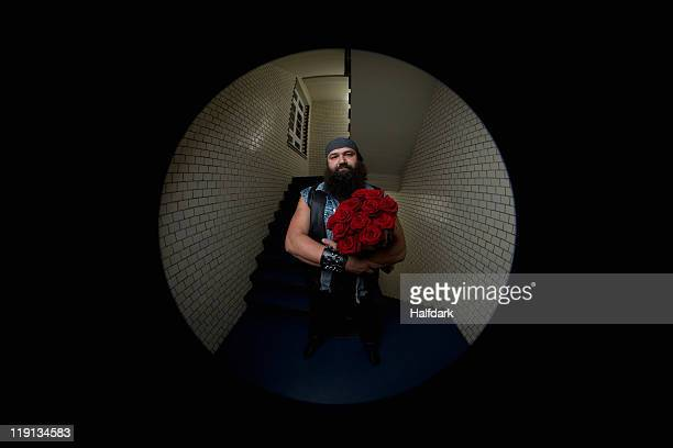 A man with roses viewed through a peephole