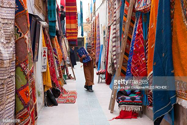 Man with rugs in market, Essaouira, Morocco