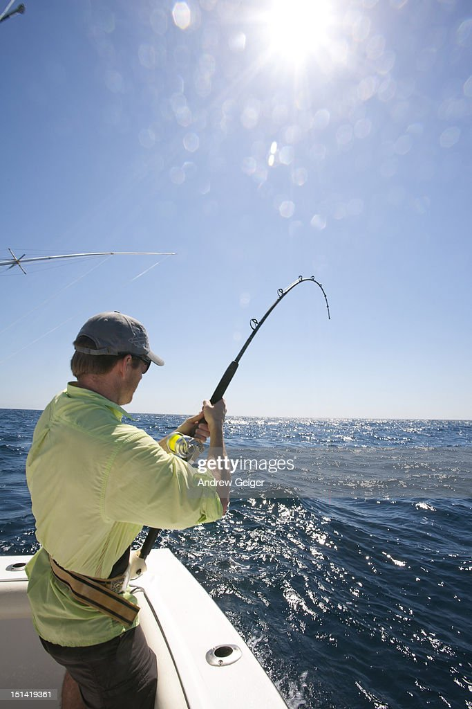 Man with Sailfish on bending fishing rod on boat.