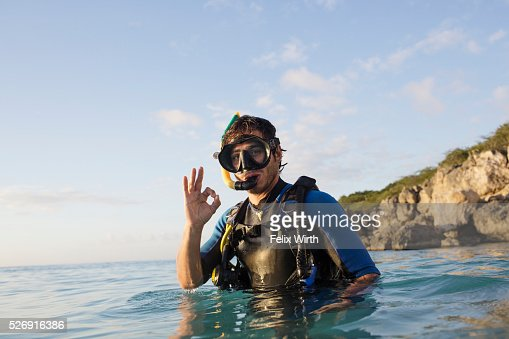 Man with scuba diving equipment in sea showing ok sign : Foto de stock