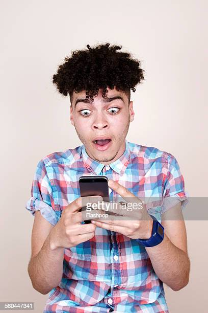 Man with shocked expression looking at phone