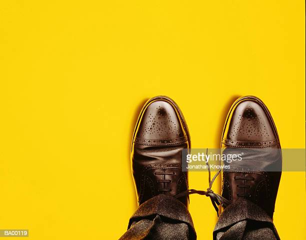 Man with shoelaces tied together, overhead view