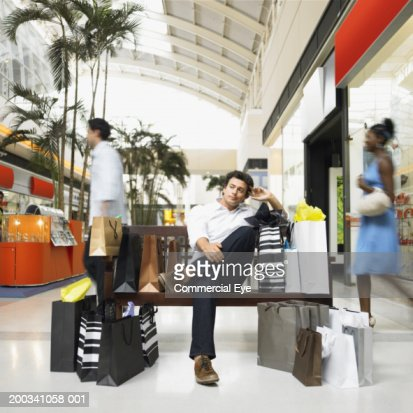 Man with shopping bags sitting on bench in mall : Stock Photo