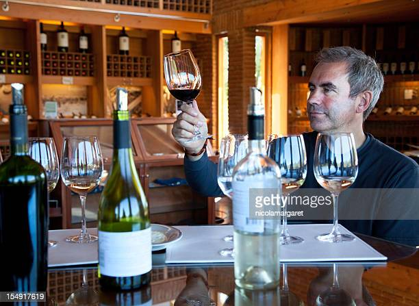 A man with short hair tasting fine wines at a winery