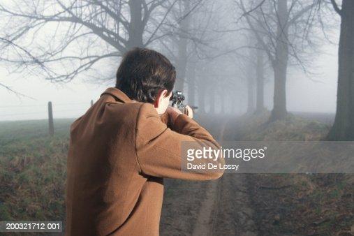 Man with shotgun aiming outdoors, rear view