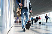 Man with shoulder bag and hand luggage walking in airport terminal, photo with men's legs walking in airport terminal