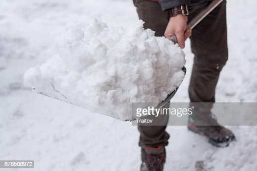 Man with shovel cleaning snow filled backyard outside his house. : Stock Photo