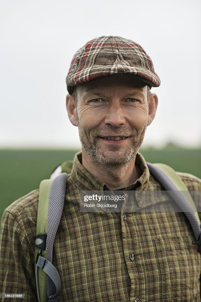 Man with sixpence and rucksack smiling