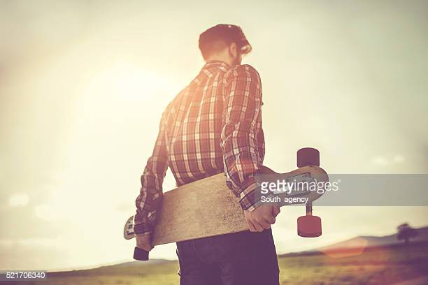 Man with skateboard under the sun