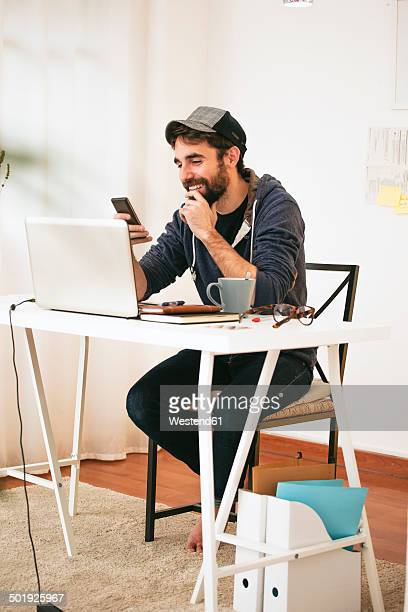 Man with smartphone at modern home office