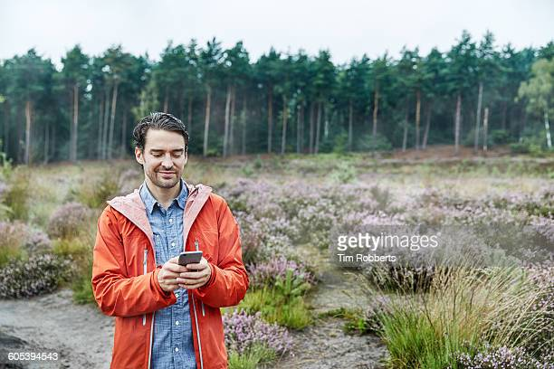 Man with smartphone in landscape