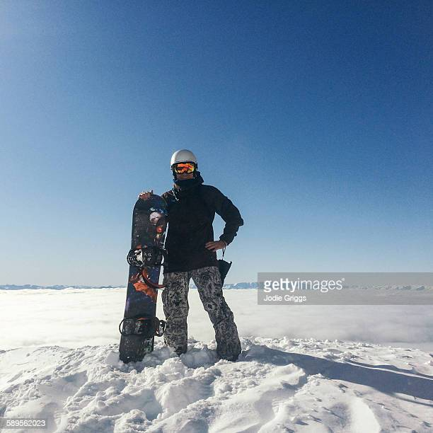 Man with snowboard standing on mountain top