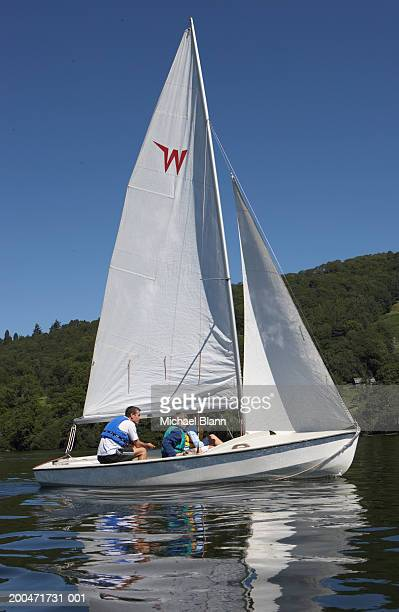 Man with son and daughter (12-14) on small sailboat