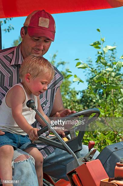 man with son driving tractor