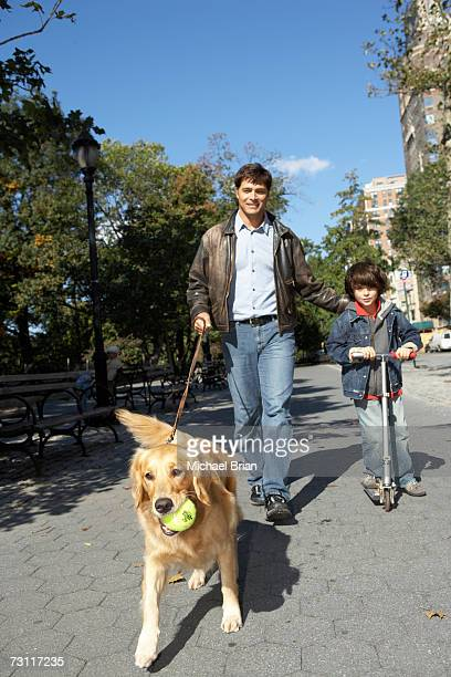 Man with son (6-7) on scooter, walking dog