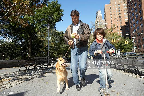 Man with son (6-7) on scoote,r walking dog