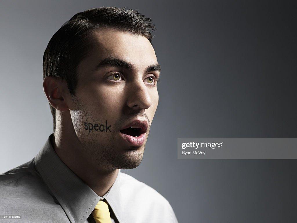 man with 'speak' written on face : Stock Photo