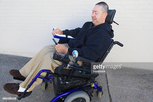 Man with spinal cord injury and arm with nerve damage in motorized wheelchair looking at smart phone
