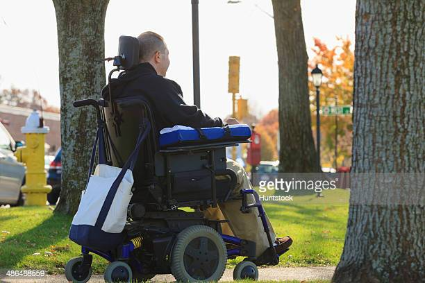 Man with spinal cord injury and arm with nerve damage in motorized wheelchair in a public park