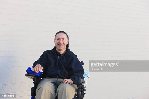 Man with spinal cord injury and arm with nerve damage in motorized wheelchair