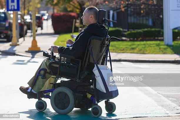 Man with spinal cord injury and arm with nerve damage in motorized wheelchair crossing public street