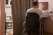 Man with spinal cord injury at sink in an accessible bathroom