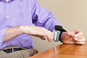 Man with spinal cord injury checking his blood pressure gauge on his wrist