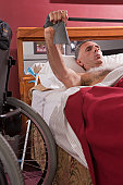 Man with spinal cord injury exercising in the bed
