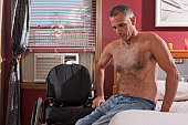 Man with spinal cord injury getting into bed from his wheelchair