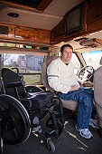 Man with spinal cord injury getting into the driver's seat from his wheelchair in accessible van